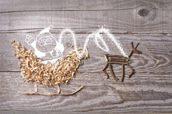 Simple symbols of Father Christmas sleigh arranged from sawdust and reindeer made from dry wooden sticks on wooden grey background Royalty Free Stock Photo