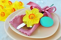 Easter table setting with pastel blue dyed egg. Simple table setting arrangement with cream porcelain dishes, pastel blue Easter egg, yellow daffodil flower Royalty Free Stock Images