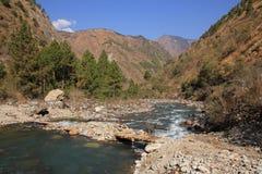 Simple timber bridge and Langtang Khola, river in Nepal. Timber bridge and Langtang Khola, river in Nepal. Scene near Shyaphru Besi. Langtang National Park Stock Image