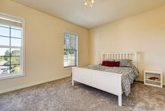 Simple upstairs bedroom with soft peach walls, gray carpet Stock Photo