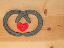 Simple Valentine design with two horseshoes. Forming a heart shape and two rings on rustic wood background with copy space Stock Images