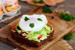 Simple vegetable salad and poached egg sandwich. Poached egg on rye bread slice with fresh vegetable salad on a wooden board. Egg weight loss recipe. Healthy egg Stock Photo