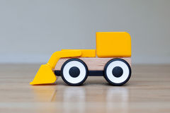 Simple wheel dozer toy. Plastic and wood stock images