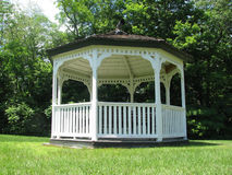 Simple white gazebo. Manicured lawn, dense forest Royalty Free Stock Images