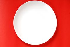 Simple white plate on a red background royalty free stock images