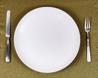 Simple white plate with silverware for dinner setting on table c Stock Images