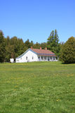 Simple white ranch house. And green meadow Royalty Free Stock Images