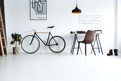 Simple, white room with bike. Simple white room for minimalist hipster working as freelancer with workplace with bombilla and vintage bike stock photo