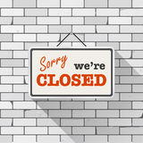 Simple white sign with text `Sorry we`re closed` hanging on a gray brick wall. Creative business interior template. Simple white sign with text `Sorry we`re Royalty Free Stock Images