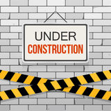 Simple white sign with text `Under Construction` hanging on a gray brick wall with warning tapes. Engineering concept. Simple white sign with text `Under Stock Images