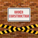 Simple white sign with text `Under Construction` hanging on a red brick wall with warning tapes. Brickwork background. Royalty Free Stock Photos
