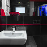 Simple white sink in bathroom. Simple white sink in modern bathroom with black wall tiles stock images