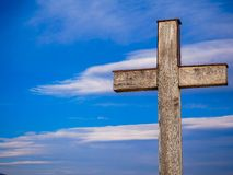 Simple wood catholic cross, blue sky with white clouds background royalty free stock image