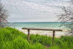 A simple wooden bench on the beach. Wild coast, bright juicy green grass, beautiful view of the sea in the spring Stock Photography