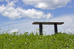 Simple Wooden Bench on a perfect Summer Day. A simple wooden bench in a park at the top of a hill on a perfect summer day Stock Images