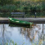Simple wooden boat at the wooden pier on the pond. stock photo