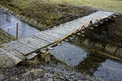 Simple wooden bridge across regulated stream Stock Photo