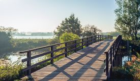 Simple wooden bridge with planks over a narrow Dutch river in th royalty free stock photo