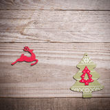 Simple wooden Christmas tree and red flying reindeer  on a green Stock Photography