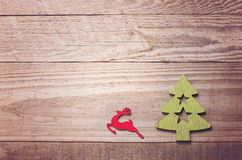 Simple wooden Christmas tree and red flying reindeer  on a green Royalty Free Stock Photos