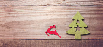 Simple wooden Christmas tree and red flying reindeer  on a green Royalty Free Stock Images