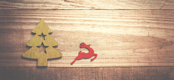 Simple wooden Christmas tree and red flying reindeer  on a green Stock Image