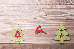 Simple wooden Christmas trees and red flying reindeer  on a gree Stock Photo