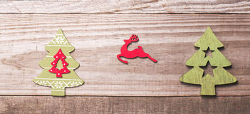 Simple wooden Christmas trees and red flying reindeer  on a gree Royalty Free Stock Photography
