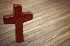 A Simple Wooden Cross on a Wooden Background Stock Images
