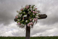 Simple Wooden Cross with a Wreath of White and Pink Silk Tulips Royalty Free Stock Photos