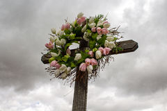 Simple Wooden Cross with a Wreath of White and Pink Silk Tulips Royalty Free Stock Photo