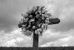 Simple Wooden Cross with a Wreath of White Silk Tulips in black Stock Image