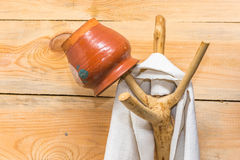 Simple wooden hanger. Simple wooden hanger with a linen towel and a clay pot Royalty Free Stock Photo
