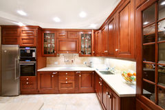Simple wooden kitchen cupboards, countertops, refrigerator. And oven in kitchen Stock Photography