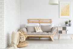 Sofa in apartment. Simple wooden sofa with DIY lights in white apartment stock images