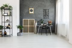 Simple workspace on gray wall. Simple workspace on gray textured wall with metal clock in freelancer`s apartment Royalty Free Stock Photos