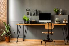 Simple workspace interior with wooden chair at the desk standing. Against black wall in a room with plants. Real photo stock photo