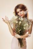Simplicidade. Mulher graciosa elegante com o ramalhete das flores que levantam no estúdio imagem de stock royalty free