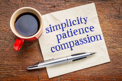 Simplicity, patience, and compassion. Simplicity, patience, compassion - three words from Buddha teaching - handwriting on a napkin with cup of coffee against stock images