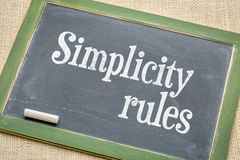 Simplicity rules  blackboard sign. Simplicity rules sign - white chalk text on a vintage slate blackboard  against burlap canvas Royalty Free Stock Photos