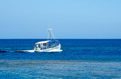 Simplicity and variations of blue colour on this image with the. Small fishing boat while floating the waters Royalty Free Stock Photos