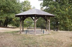 Simplicity wooden shelter with seats in nature, small gazebo for tired tourists stock photos