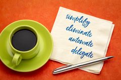 Simplify, eliminate, automate, delegate concept on napkin. Simplify, eliminate, automate, delegate productivity concept - inspirational handwriting on a napkin stock photos