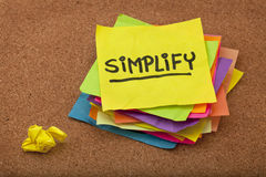 Simplify reminder. Pragmatic or get organized concept, simplify reminder - a stack of colorful sticky notes on cork bulletin board stock photo