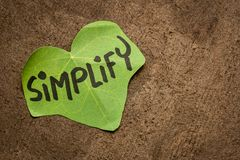 Simplify reminder note. Simplify reminder - handwriting on a leaf shaped note against bark paper with a copy space royalty free stock photos