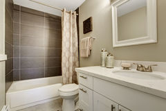 Simplistic bathroom wth grey and white theme. Simplistic bathroom with grey and white theme, along with full bath shower Stock Photos