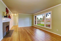 Simplistic family room with hardwood floor. Simplistic family room with fireplace, hardwood floor, and window Stock Photography