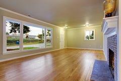 Simplistic family room with hardwood floor. Simplistic family room with fireplace, hardwood floor, and window Stock Photos