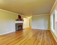 Simplistic family room with hardwood floor. Simplistic family room with fireplace, hardwood floor, and window Royalty Free Stock Images