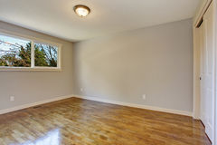 Simplistic hardwood bedroom. Simplistic hardwood bedroom with great lighting and closet Royalty Free Stock Image